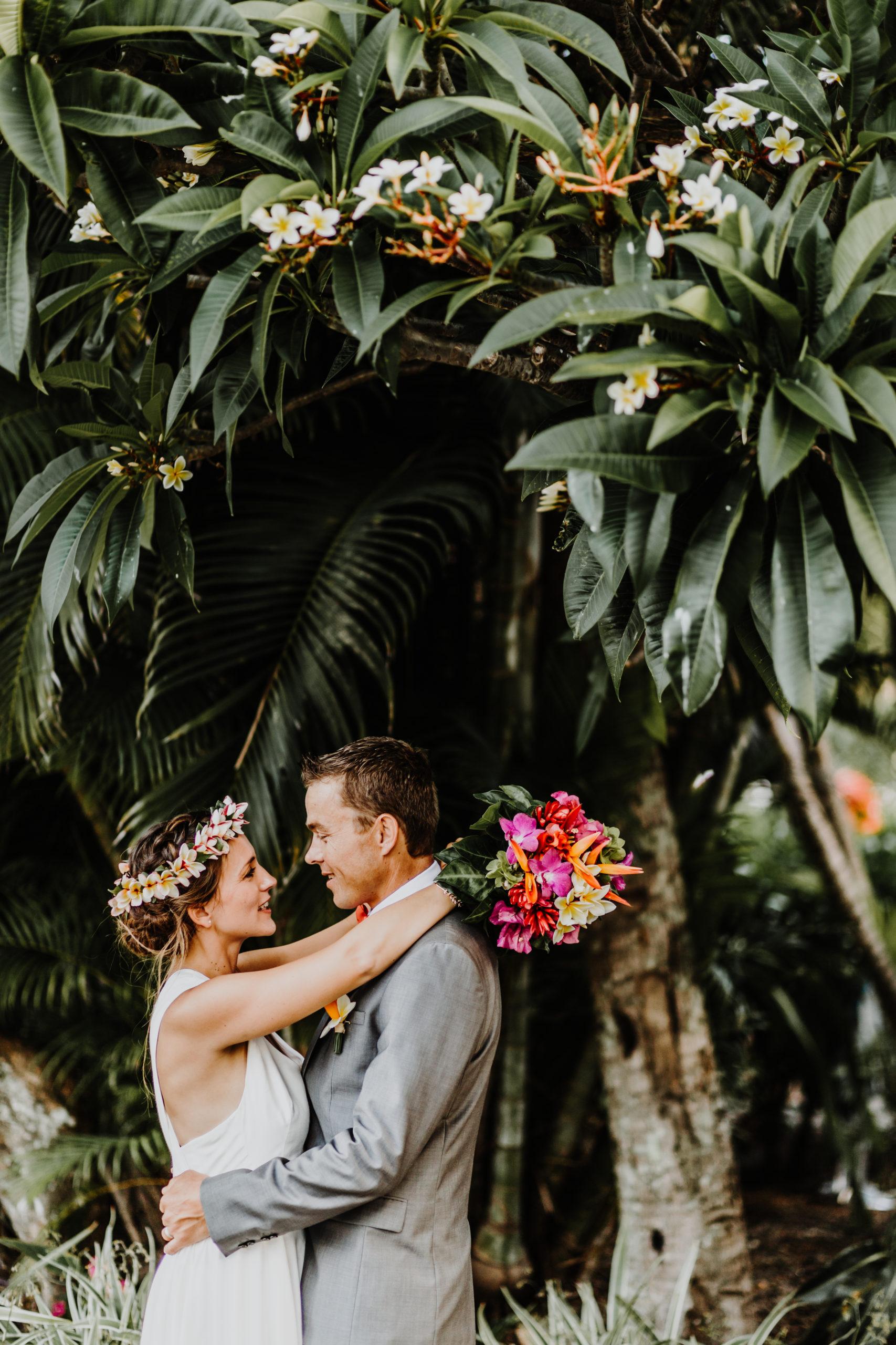 couple de mariés face à face, sous un arbre tropical