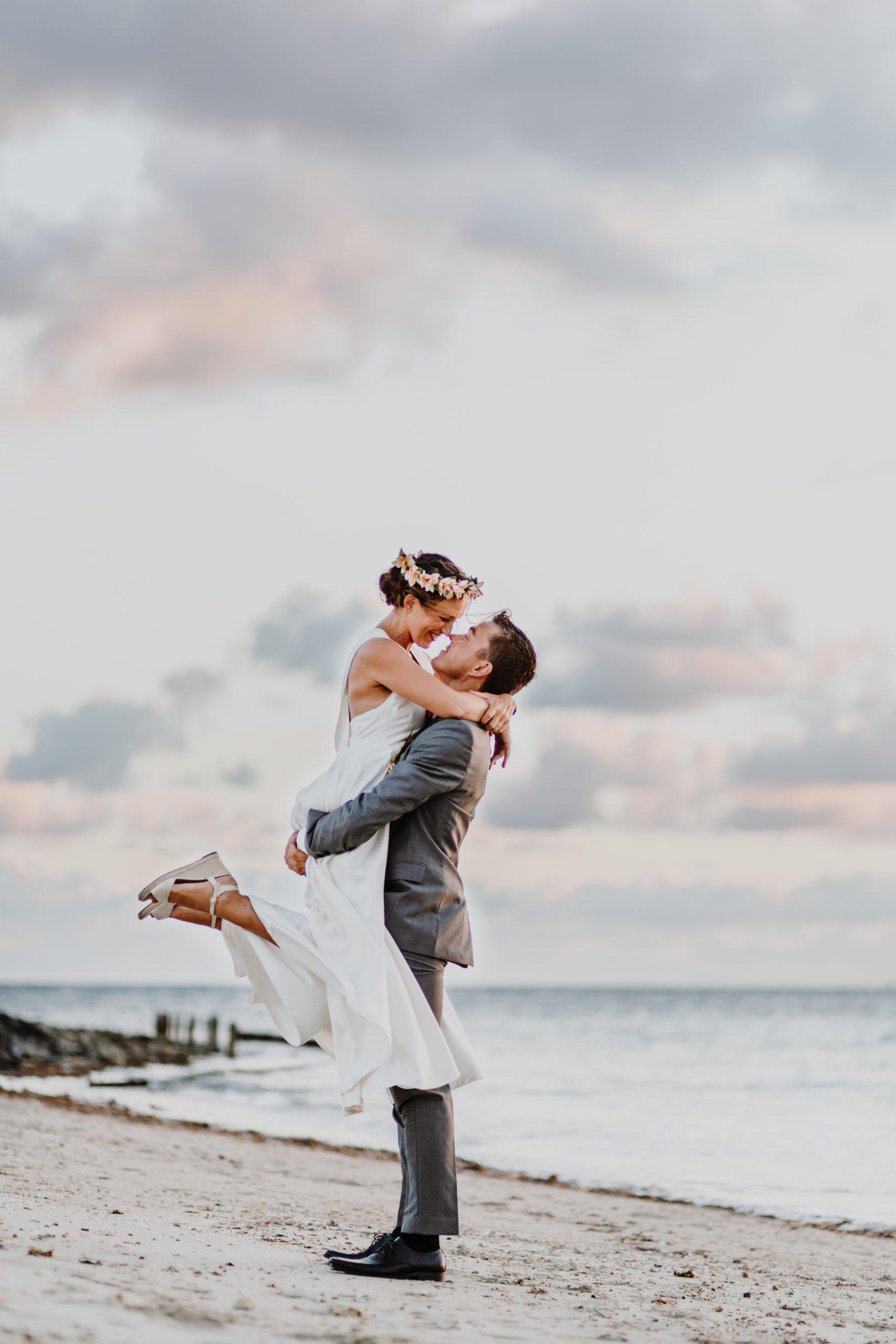 couple de mariés sur la plage, le mariés porte la mariée devant un coucher de soleil
