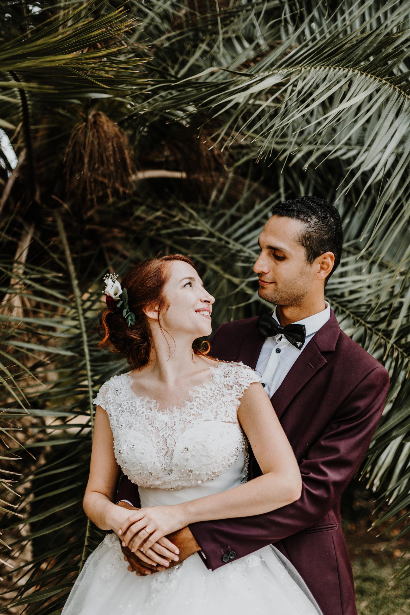 couple de mariés se regardent, enlacés dans la végétation