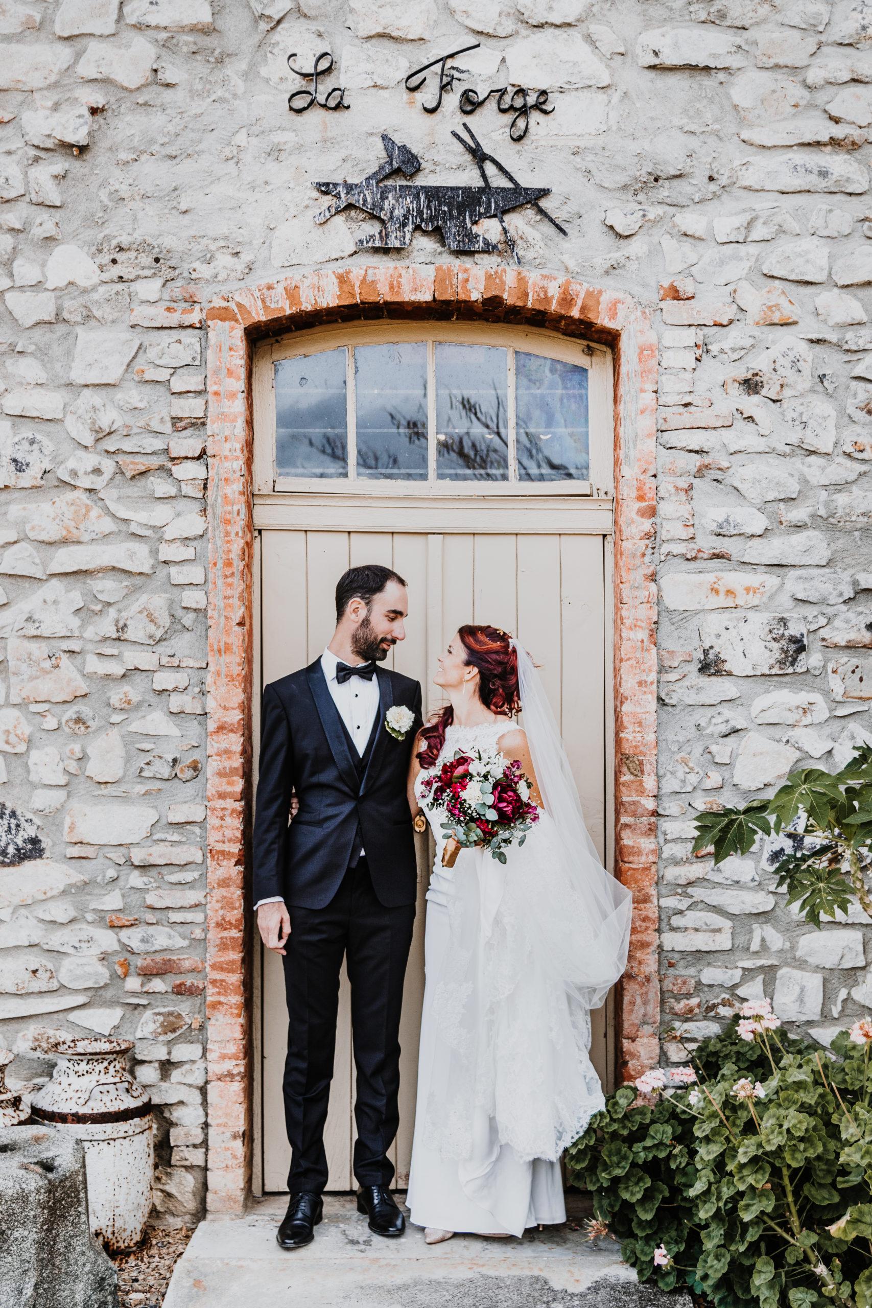 couple de mariés côte à côte, se regarde devant un mur en pierres
