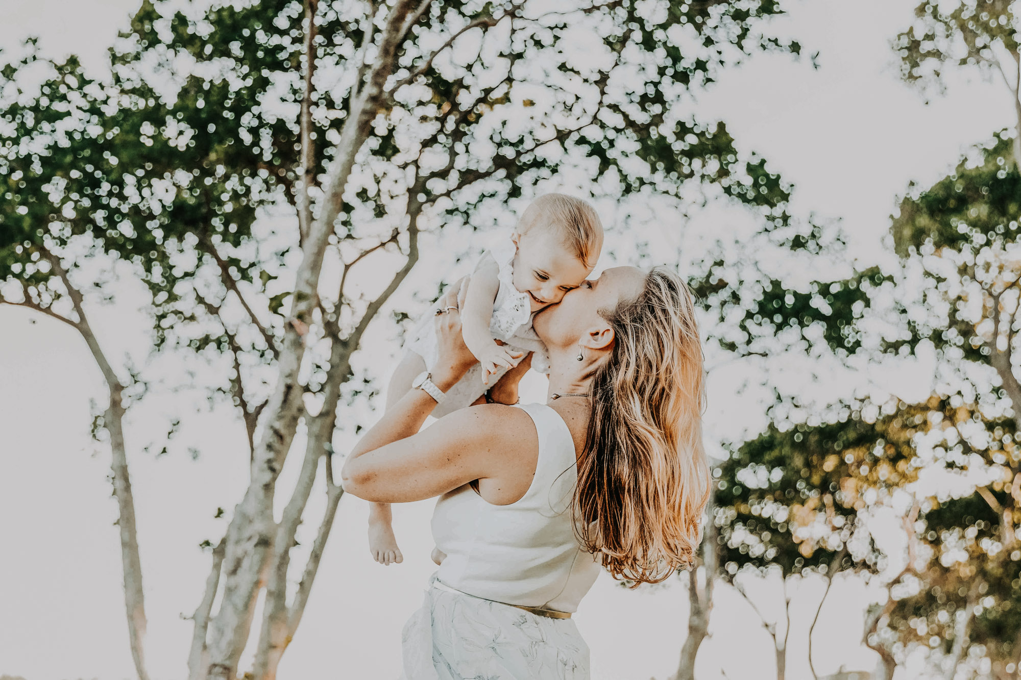 une femme porte sa petite fille dans les airs