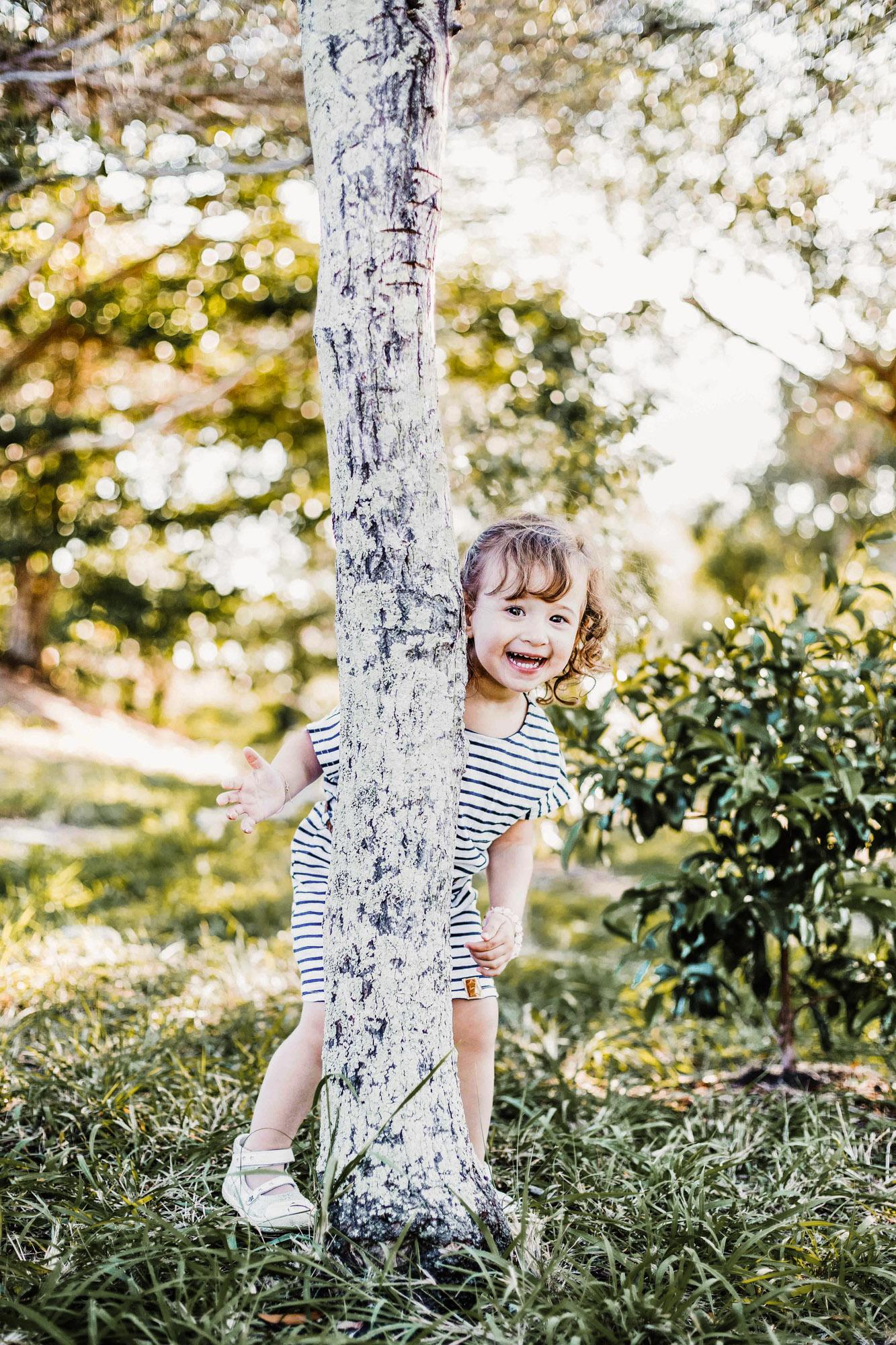 petite fille joue dans la forêt, se cache derrière un arbre et rigole