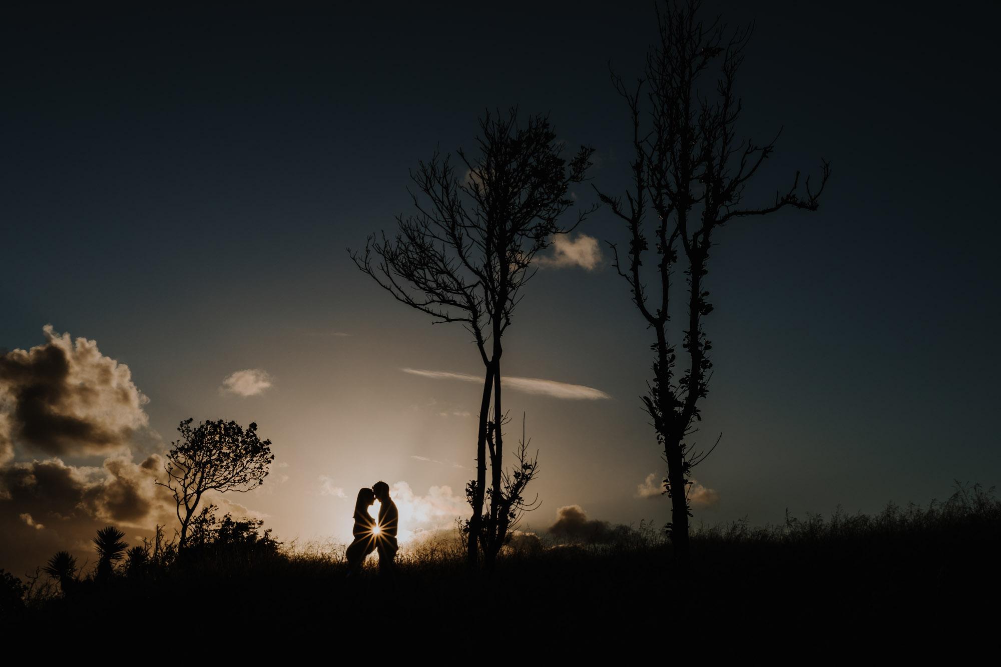 silhouette d'un couple en contre jour au coucher du soleil, la femme est enceinte