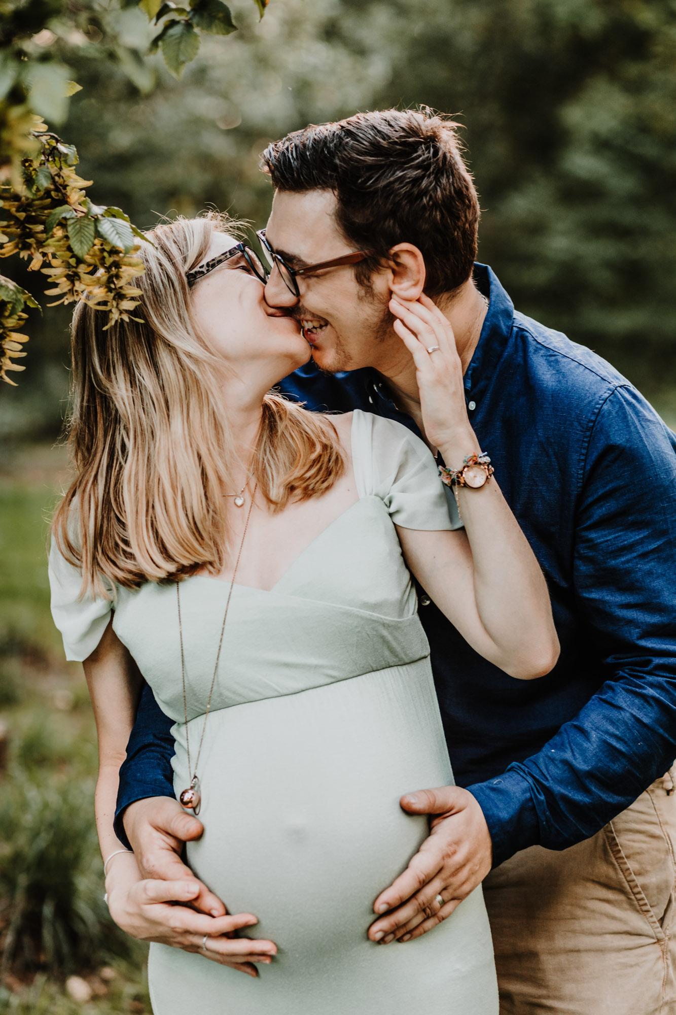 une femme enceinte et son mari s'embrassent en riant, l'homme a les mains posées sur son ventre dans la foret