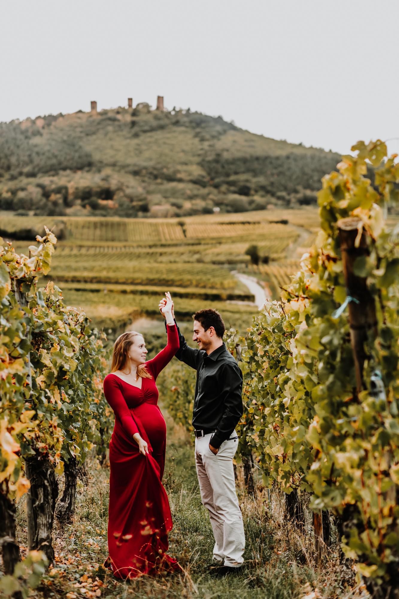 un couple et une femme enceinte dansent dans les vignes à l'automne