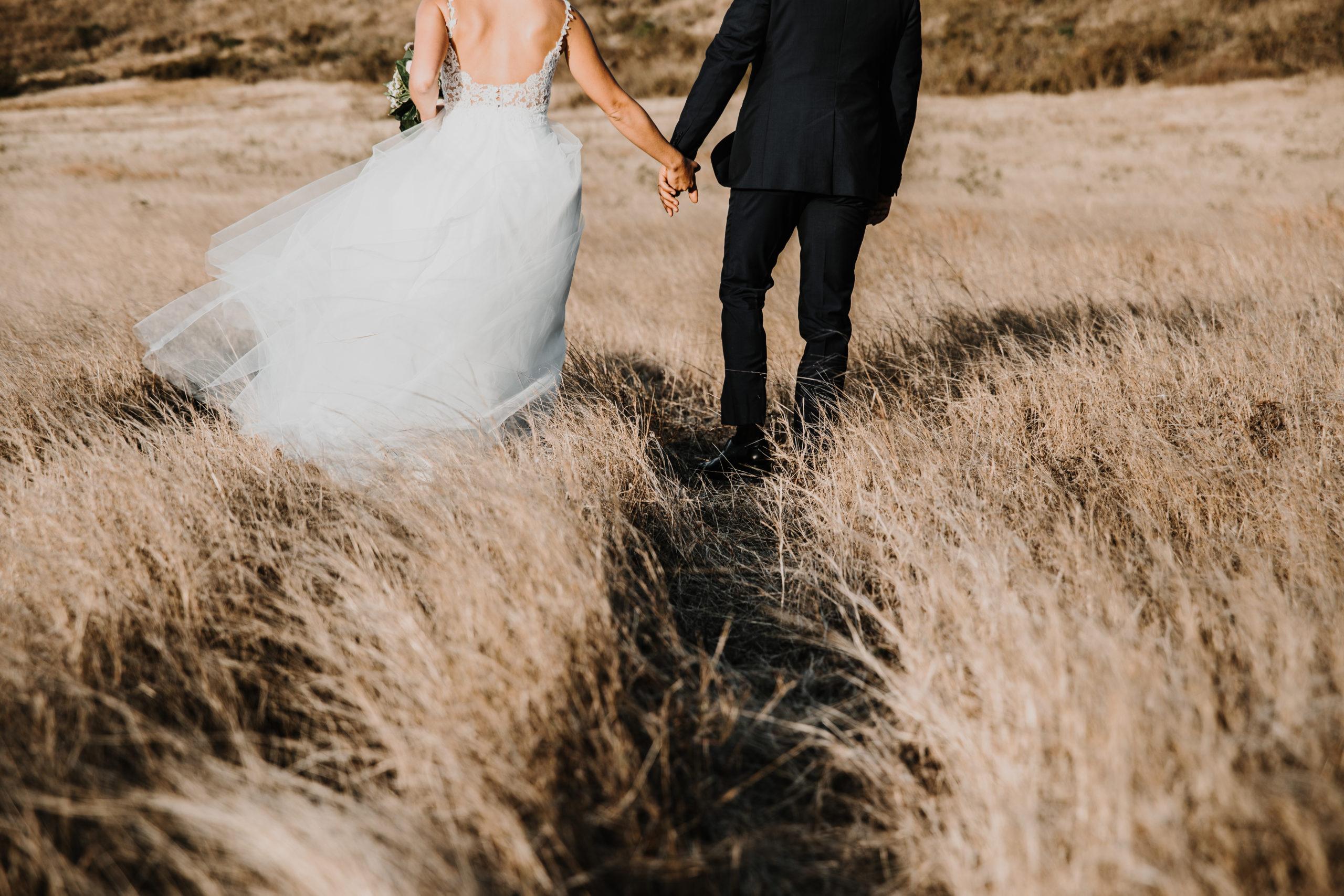 couple de mariés de dos, marchent main dans la main dans les herbes hautes
