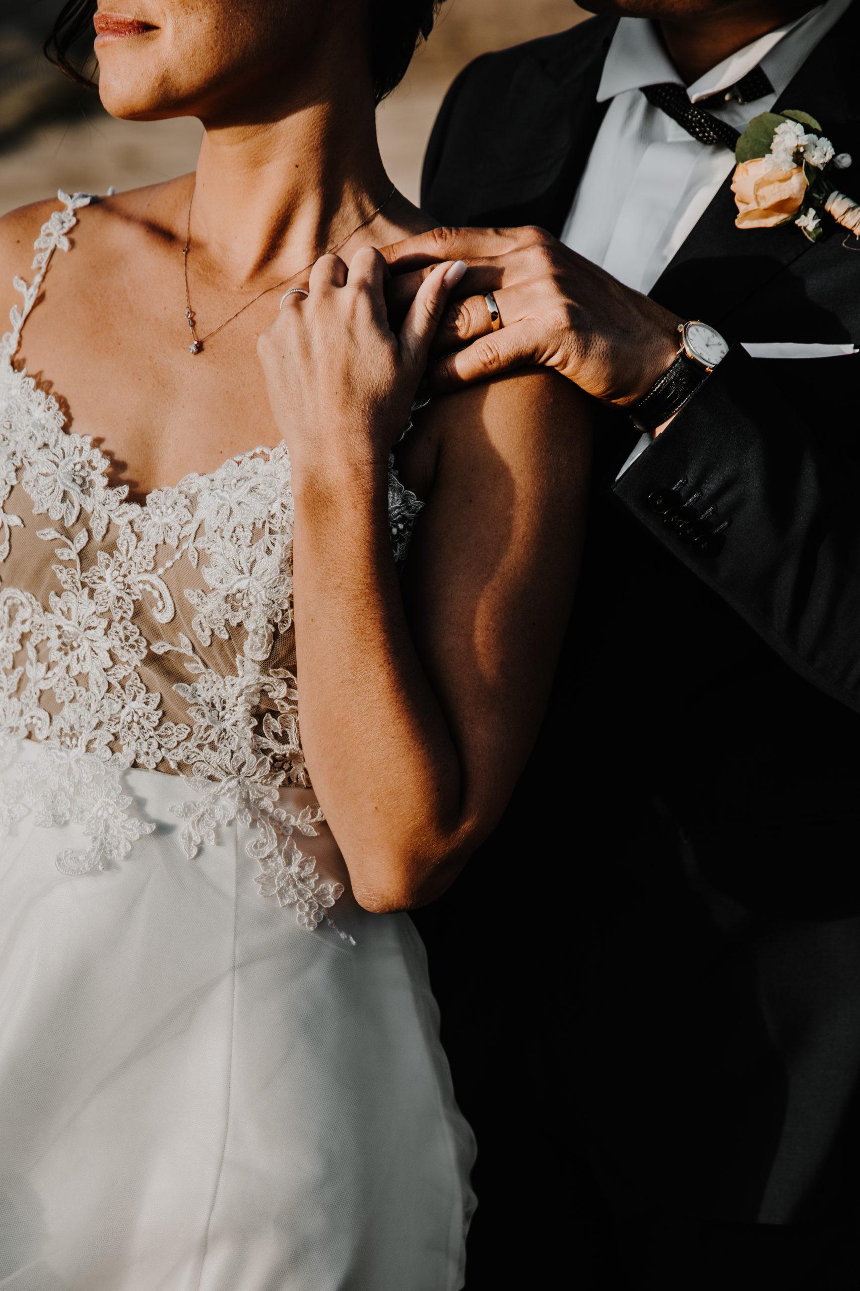 détail des mains des mariés entrelacés sur l'épaule de la mariée au coucher du soleil