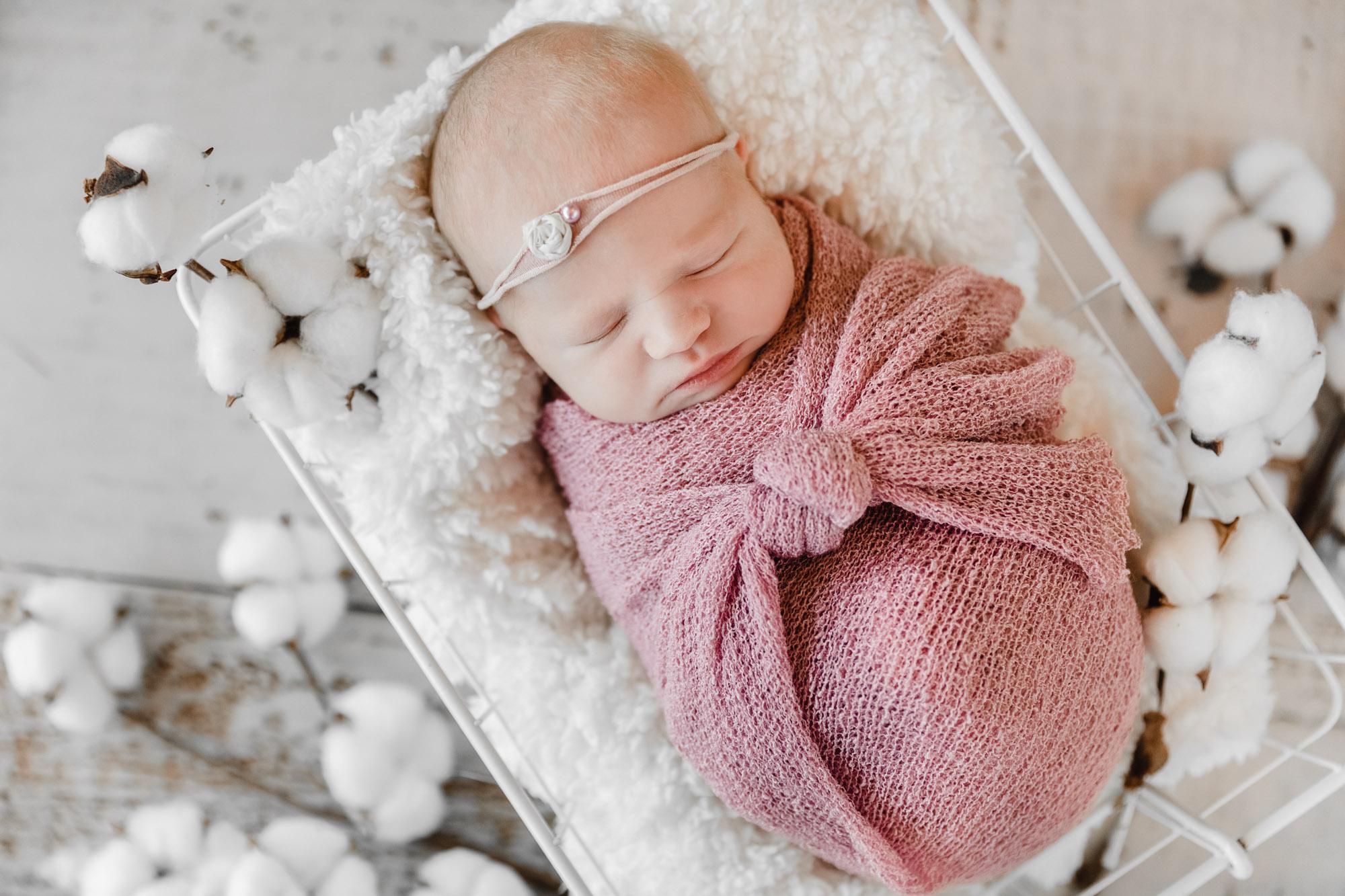 bébé endormi dans panier blanc entouré de fleurs de coton