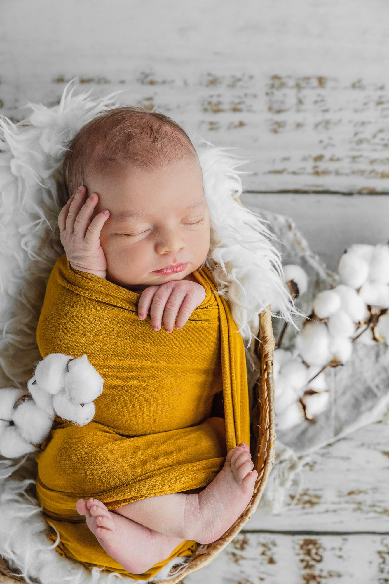 bébé emmailloté dans un tissus jaune moutarde, endormi dans un panier en osier entouré de fleurs de coton