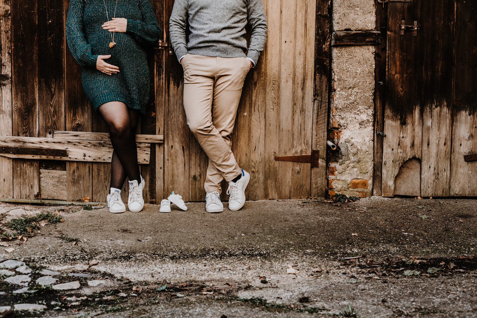 une femme enceinte et son mari adossés à un mur en bois, détail des jambes et du ventre du couple